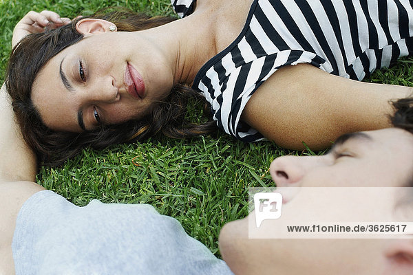 Erhöhte Ansicht eines jungen Paares liegen auf dem Rasen in einem park