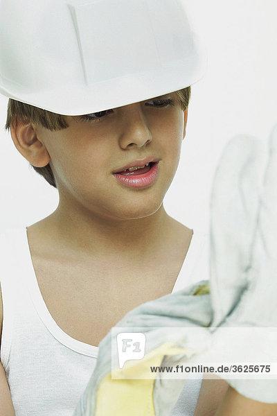 Nahaufnahme eines jungen tragen eine Bauarbeiterhelm und Handschuhe