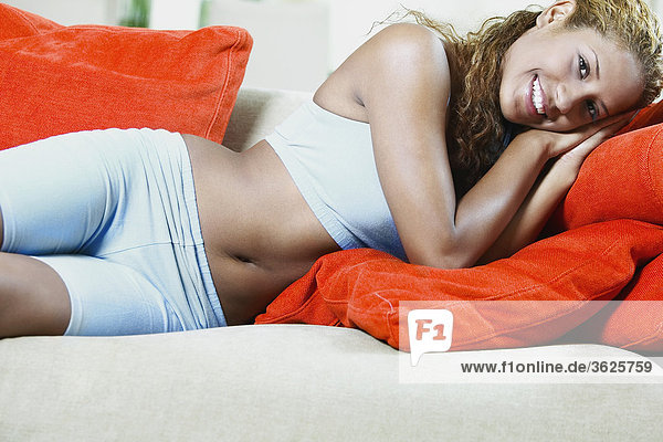 Close-up of a young woman lying on a couch and smiling