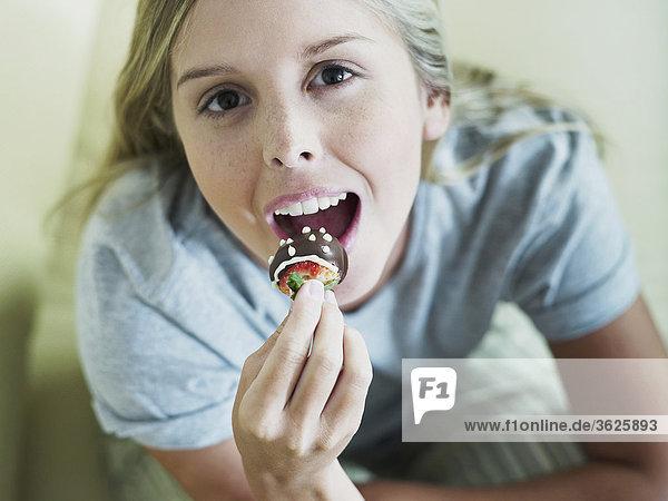 Portrait einer jungen Frau Essen ein Gebäck