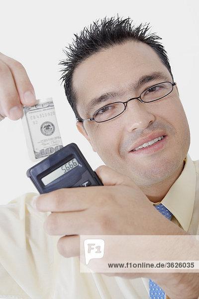 Portrait of a Geschäftsmann hält ein Rechner und ein Dollar-Schein