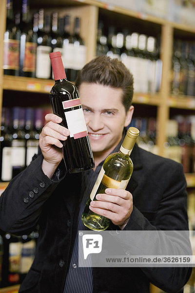Portrait of a young man holding two wine bottles in a liquor store