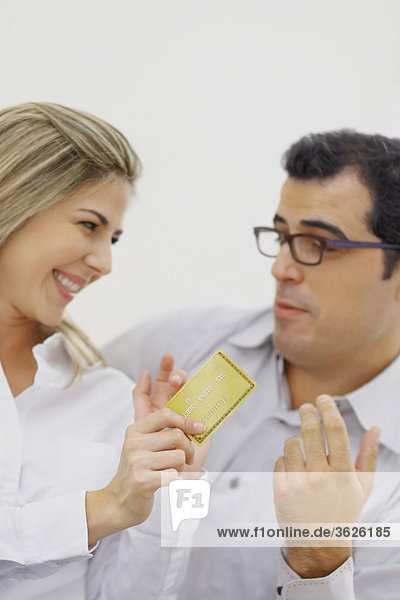 Close-up of a mid adult woman holding a credit card with a mid adult man looking at her