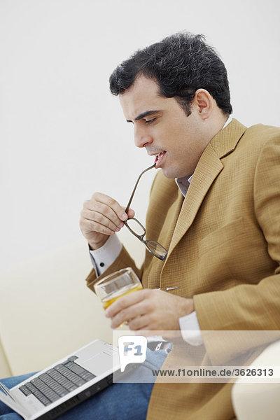 Seitenansicht eines Mitte Erwachsenen Mannes Blick auf einem Laptop und einem Glas Wein hält