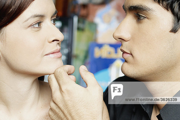 Close-up of a young man touching a young woman's chin