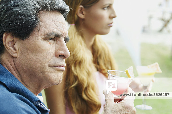 Seitenansicht einer jungen Frau und ein älterer Mann halten Gläser