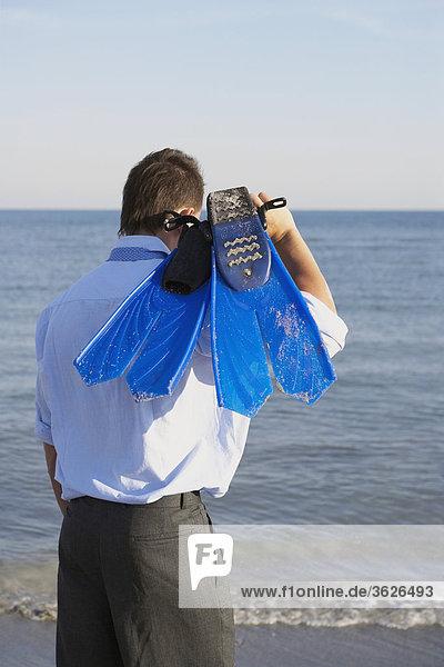 Rückansicht eines Mannes hält flossen am Strand