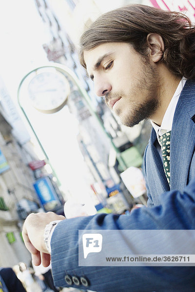 Side profile of a businessman checking the time