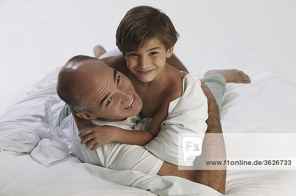 Boy mit seinem Vater auf dem Bett liegend