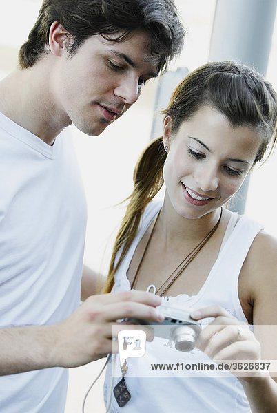 Close-up of a young couple looking at a digital camera