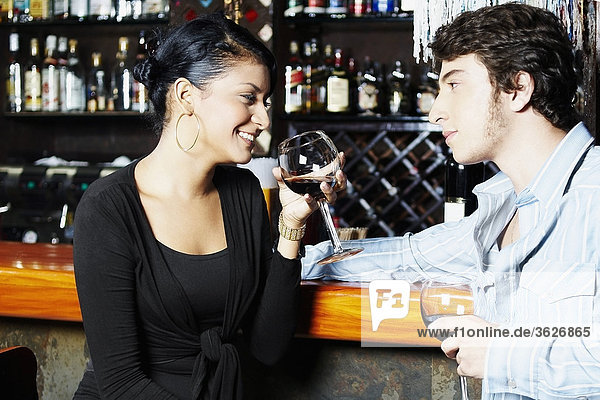 Young couple holding glasses of wine and looking at each other