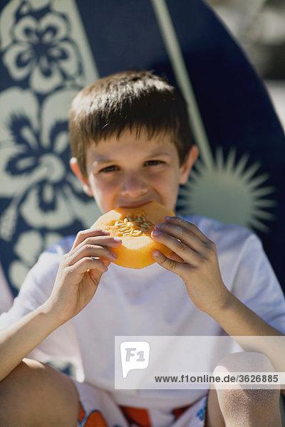 Portrait eines jungen essen ein Stück der Melone