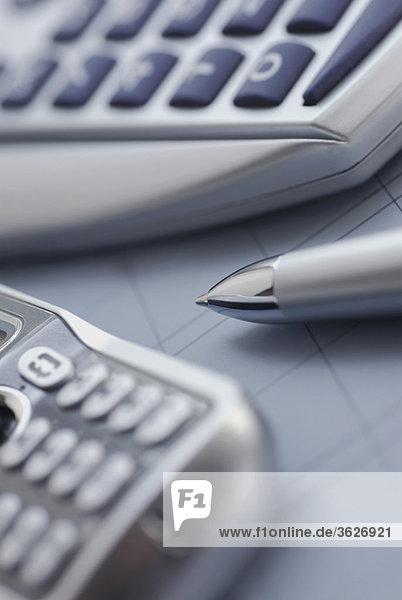 Nahaufnahme eines Mobiltelefons mit einem Kugelschreiber und einen Taschenrechner