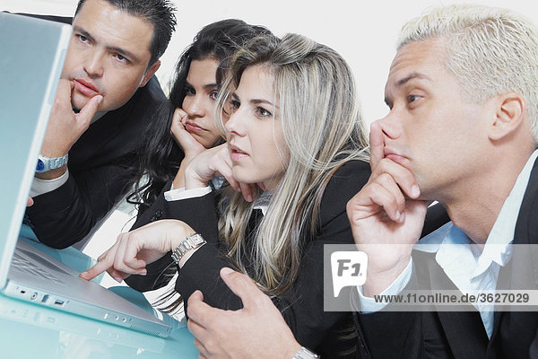 Close-up of two businessmen and two businesswomen in front of a laptop and thinking