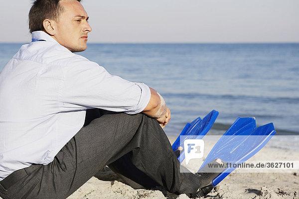 Seitenansicht eines jungen Mannes mit Flossen am Strand sitzen