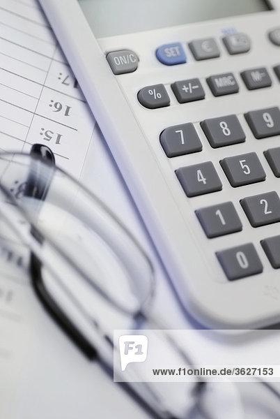 Nahaufnahme Taschenrechner mit einem Paar Brillen für ein Dokument