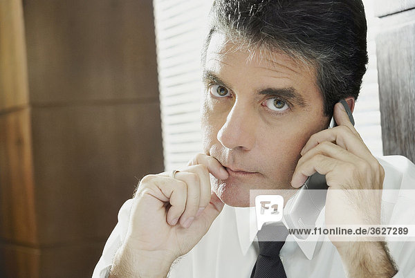Portrait of a mature man talking on a mobile phone and thinking