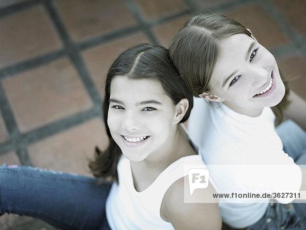 Erhöhte Ansicht ein Teenagerin und ihre Schwester Rücken an Rücken sitzen