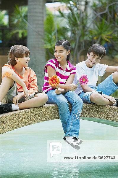 Mädchen sitzen zwischen zwei jungen auf einer Fußgängerbrücke in einem Teich
