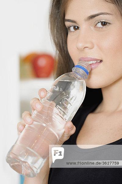 Portrait einer jungen Frau hält eine Flasche Wasser