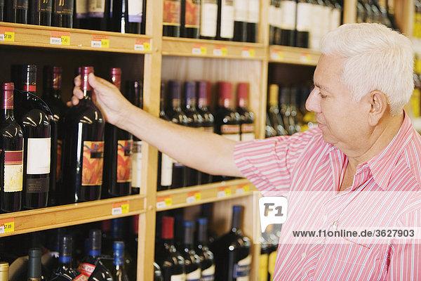 Älterer Mann Kommissionierung eine Flasche Wein aus einem Regal