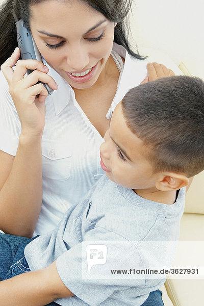 Nahaufnahme einer jungen Frau auf dem Telefon und ihrem Sohn sitzt auf ihrem Schoß