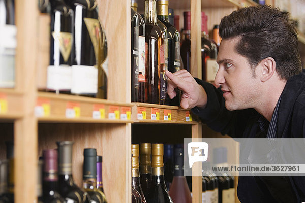Seitenansicht eines jungen Mannes Blick auf einer Weinflasche in ein Spirituosengeschäft