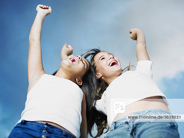 Untersicht ein Teenagerin und ihre Schwester mit ihren Armen ausgelöst
