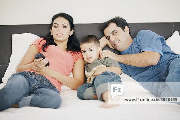 Bildnis eines Knaben mit seinen Eltern auf dem Bett liegend