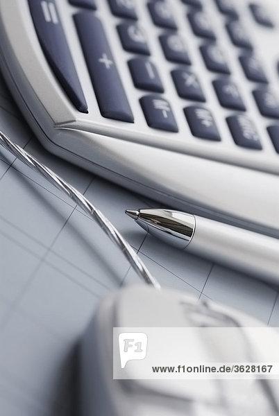 Nahaufnahme des Taschenrechners und eine Computermaus mit Kugelschreiber