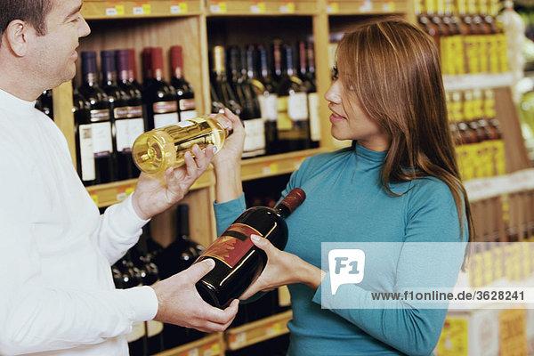 Junge Frau und ein Mitte Erwachsenen Mann Blick auf einander und hält wine bottles