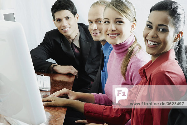 Portrait of two businesswomen and two businessmen sitting in front of a computer