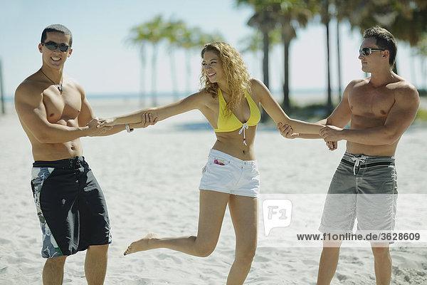 Junger Mann und eine Mitte Erwachsenen Mann  hält eine junge Frau am Strand