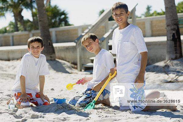 Porträt von zwei jungen und ein Spiel mit Teenager sand Eimer und Schaufel am Strand