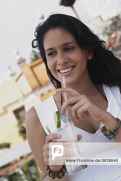 Nahaufnahme of a junge Frau hält ein Glas Cocktail und lächelnd