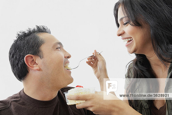 Close-up of a young woman feeding a mid adult man