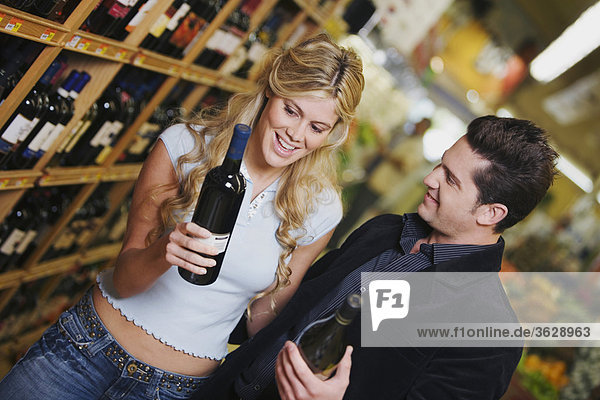 Close-up of a young couple holding wine bottles in a liquor store