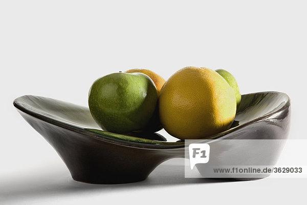 Nahaufnahme einer Granny Smith Apple und eine Orange auf einer Platte