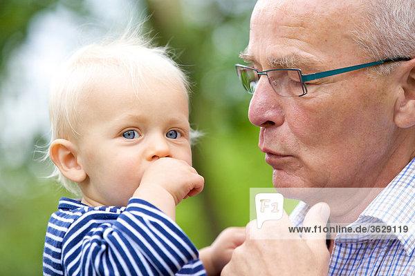 Großvater trägt Kleinkind im Freien  Portrait