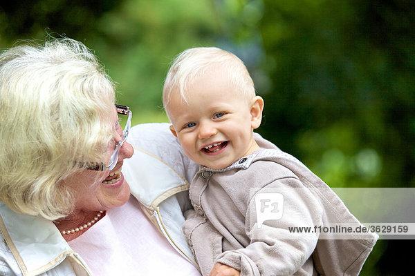 Großmutter trägt Kleinkind im Freien  Portrait