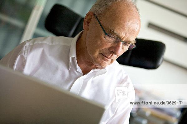Senior mit Laptop im Arbeitszimmer Heimarbeitsplatz