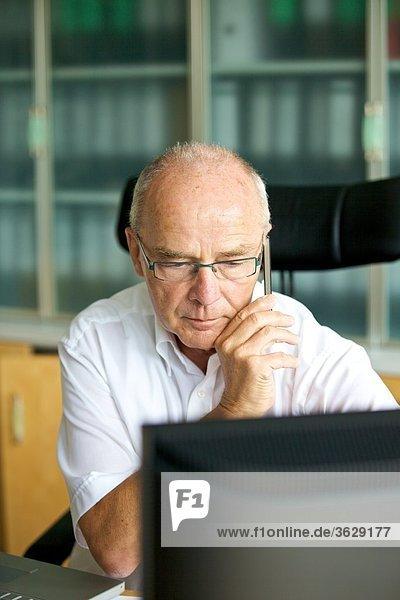 Senior telefoniert mit Handy im Arbeitszimmer Heimarbeitsplatz