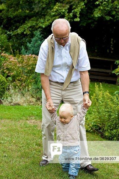 Großvater hilft Kleinkind beim Gehen