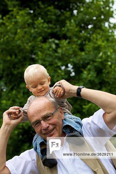 Großvater trägt Kleinkind auf den Schultern  Portrait