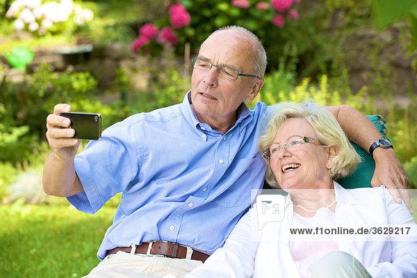 Glückliches Seniorenpaar mit Smartphone im Garten