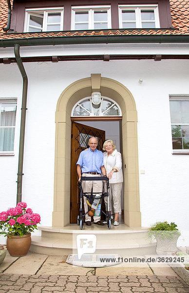 Seniorenpaar mit Rollator an der Eingangstür