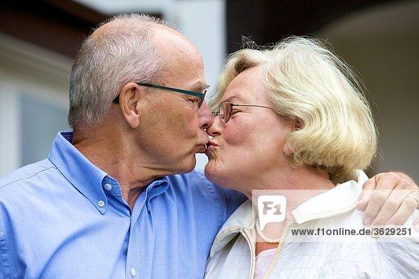 Seniorenpaar küsst sich vor Wohnhaus
