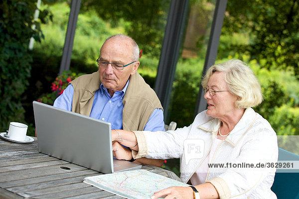 Seniorenpaar auf der Terrasse mit Laptop und Straßenkarte
