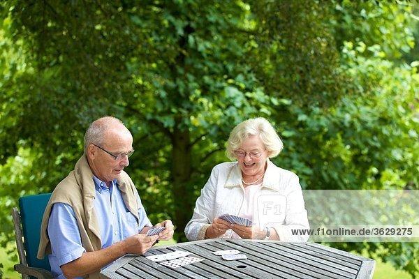 Seniorenpaar spielt Karten auf der Terrasse