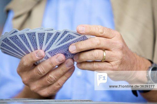 Senior spielt Karten  close-up